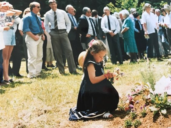 Sian beside her father's grave at the one-year memorial